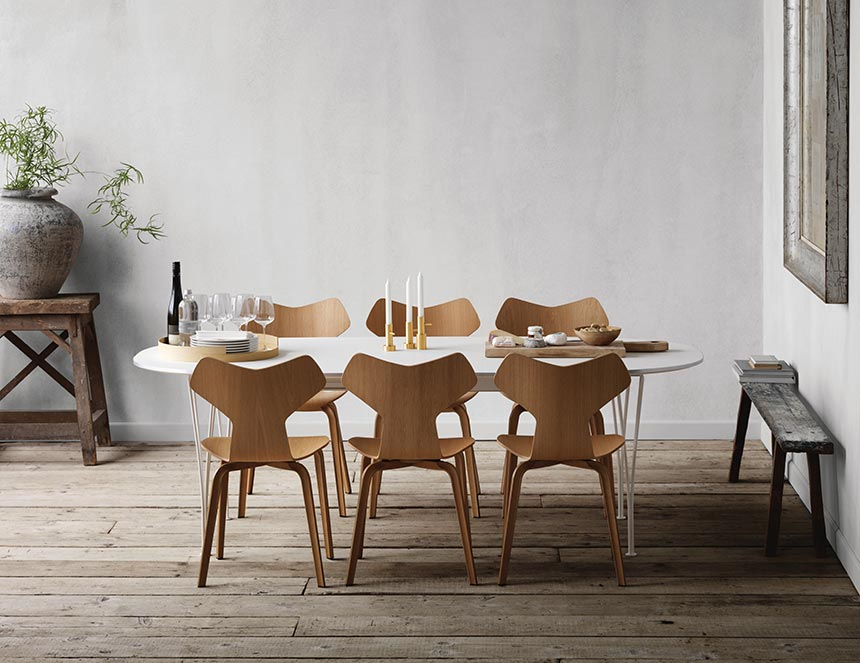 A stylish contemporary dining setup with a white dining table, light stained wooden chairs but ash gray wooden floor finish. Image by Nest.
