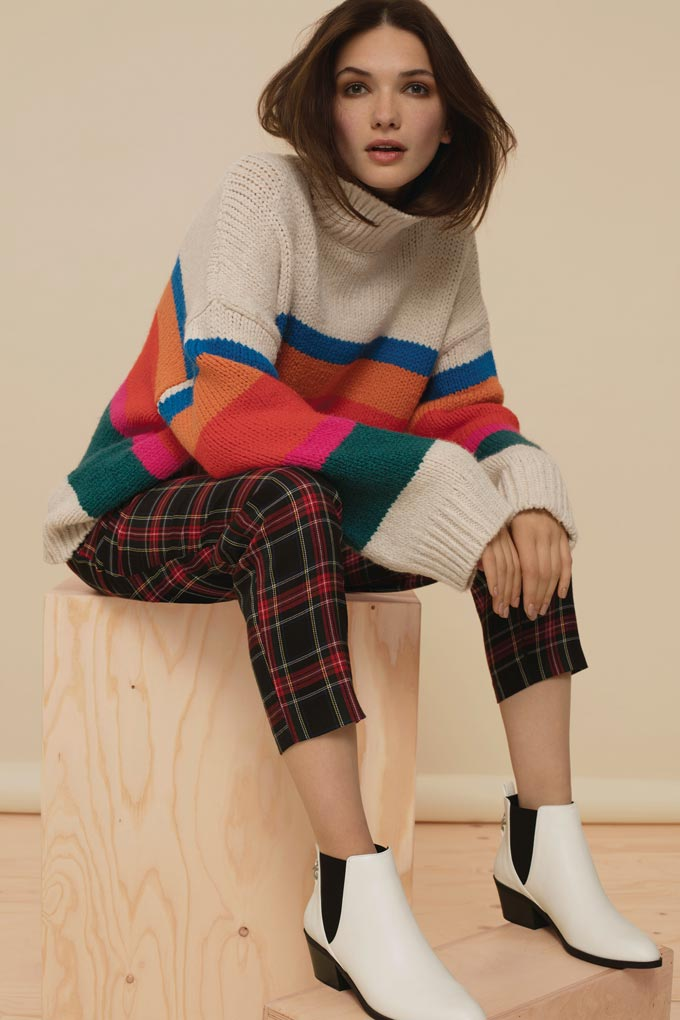 A colorful striped oversized sweater paired with a red and green tartan pair of pants. An unusual combo for a stylish outfit worn by a woman. Image by New Look.