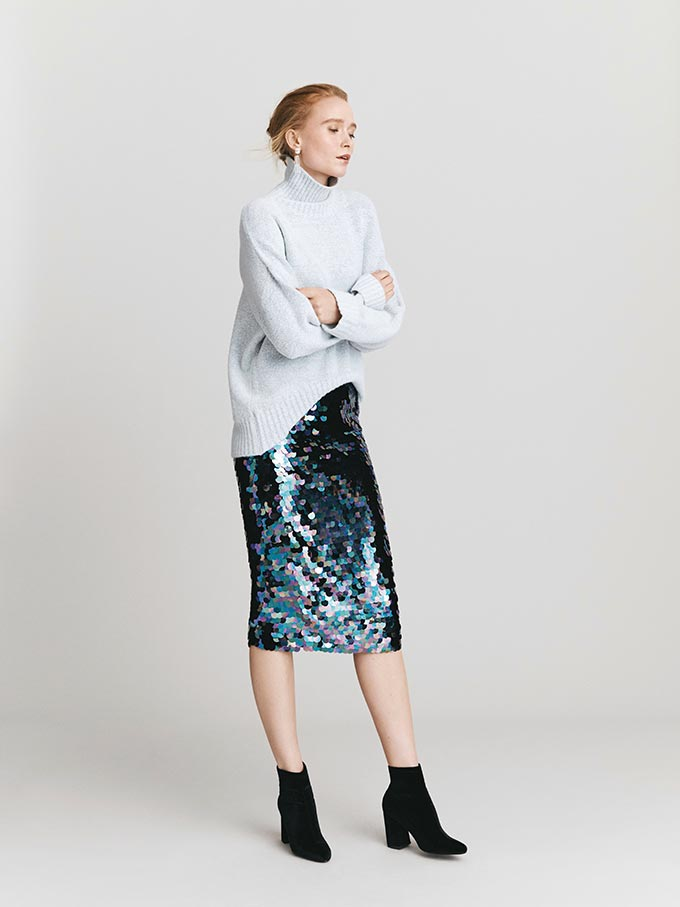 A beautiful combination. A relaxed feel sweater paired with a blue sequin skirt and black booties. I could wear that! Image by Oasis.