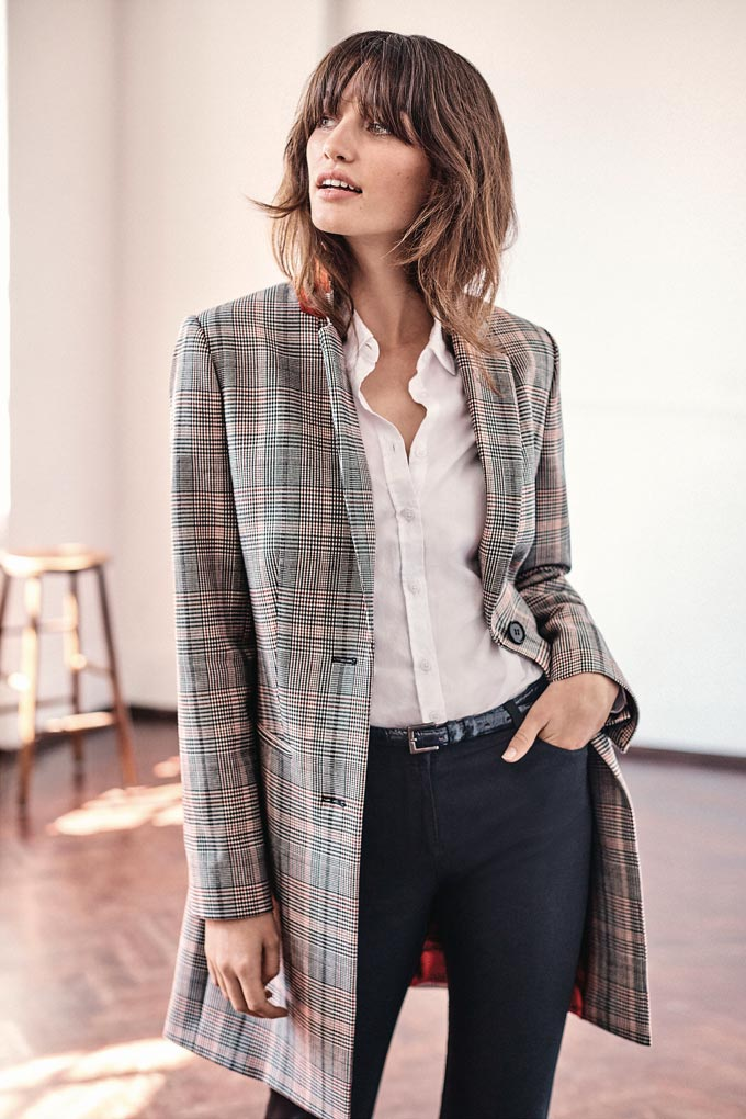 A grey plaid blazer is always a good idea, especially when paired with a white shirt and black pants as worn by this beautiful woman. A lifestyle image by Pure Collection.