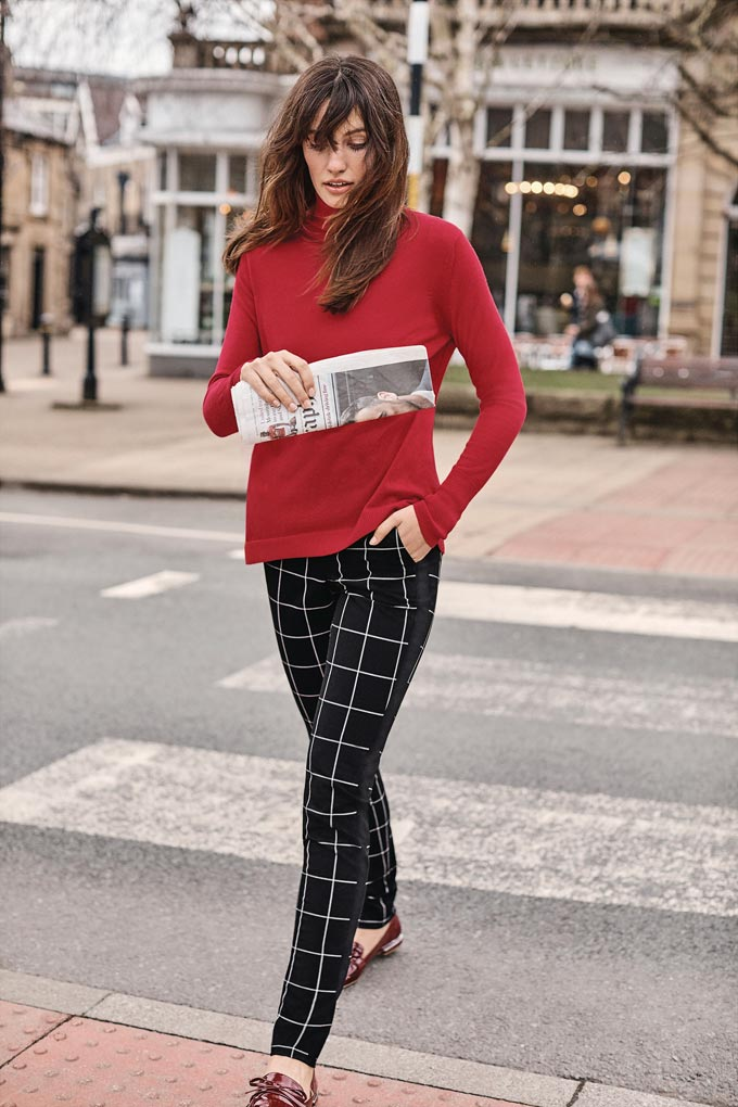 Love the combination. A woman walking in the streets wearing a red sweater with a pair of black check pants. A lifestyle image by Pure Collection.