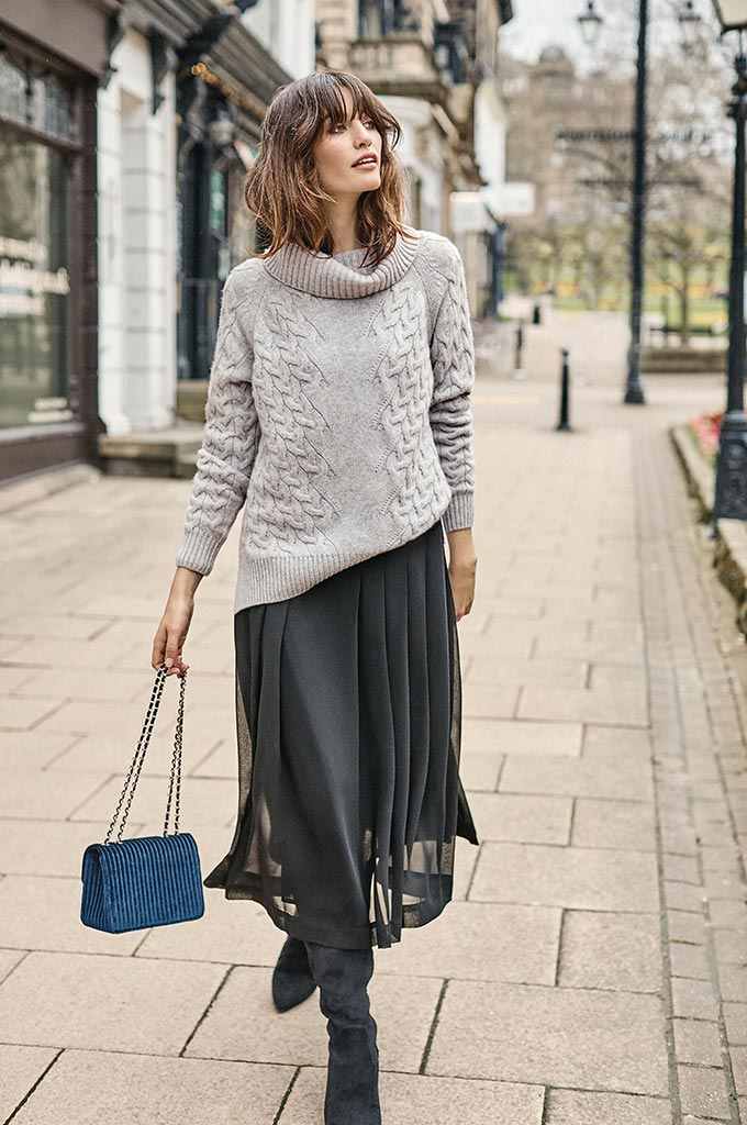 A stylish woman walking down the street in a grey knitted sweater, a black maxi skirt and suede black slouch boots. Image by Pure Collection.