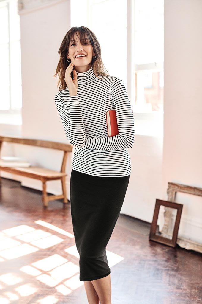Love the simplicity of this outfit. A woman wearing a Breton turtleneck with a black skirt. Image by Pure Collection.
