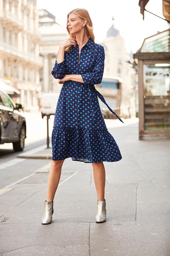 A stylish woman dressed in a blue polka dot dress and silver ankle boots standing in the middle of a street. Image by Sosandar.