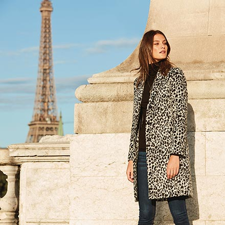 How chic! A leopard print coat over a black outfit with. In the background there's Eiffel Tower. Image by Sosandar.