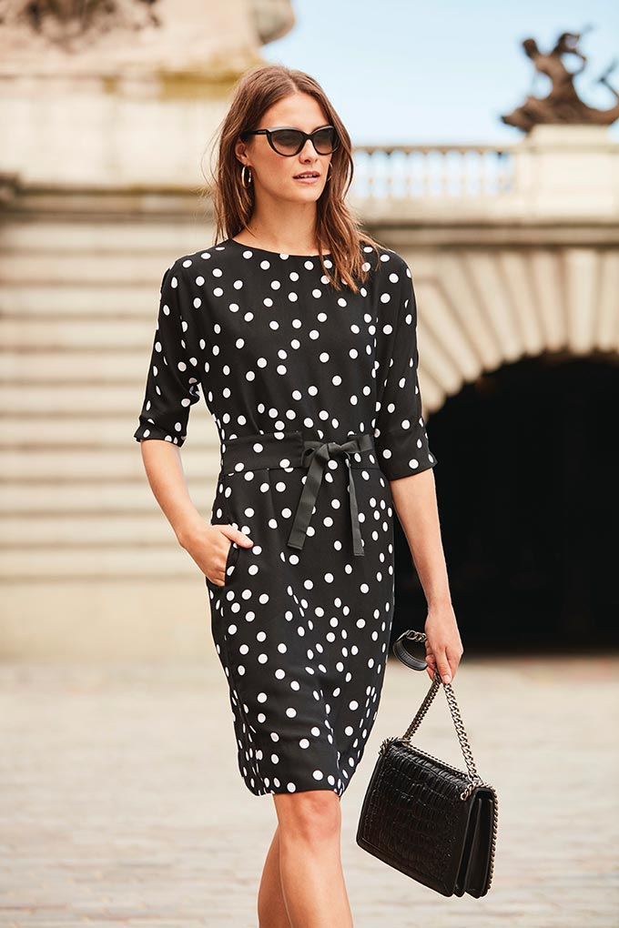 Love this black polka dot dress! How stylish! A woman is wearing it and walking somewhere in Paris. Image by Sosandar.