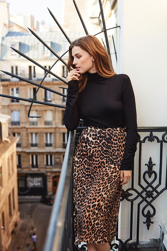 A redhead woman looking out from her Parisian flat's balcony dressed with a black top and a leopard print skirt looks quite mysterious to me. Image by Sosandar.