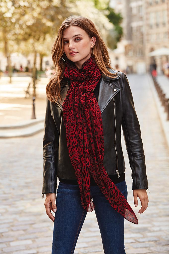 I love that print scarf combined with the black leather jacket and denims. It looks rock chic on this woman walking down the street somewhere in Paris. Image by Sosandar.