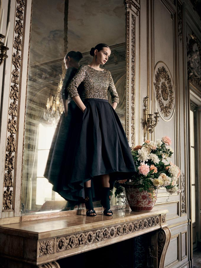 A fashion lifestyle shot with a very elegant dressed woman on top of a huge embellished fireplace mantel. Image by Veramont.