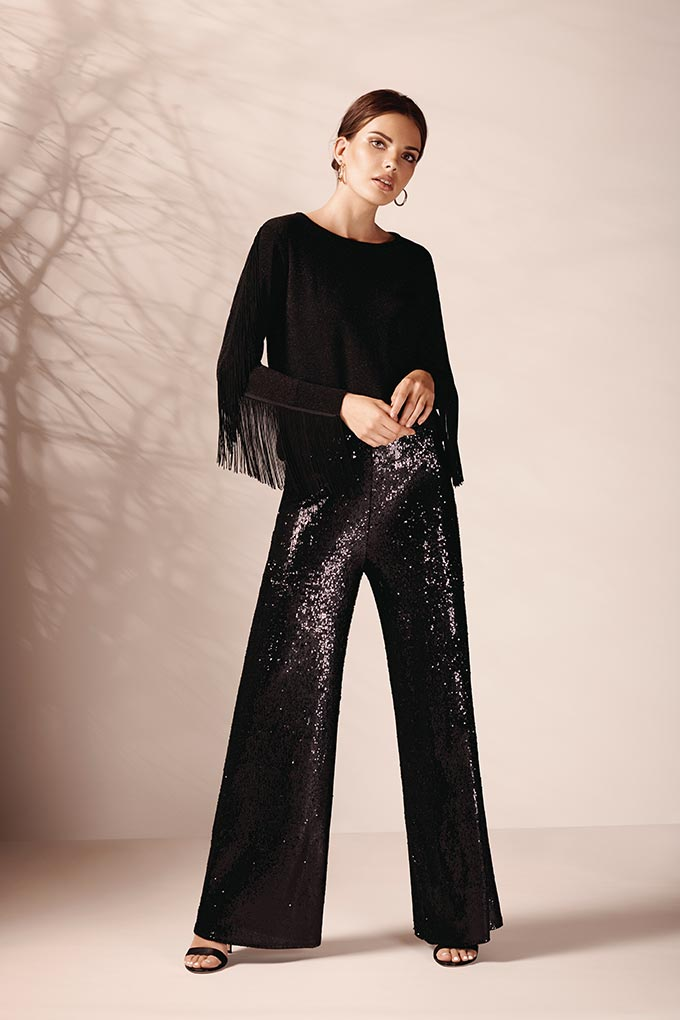 I love the fringe of this black top over the black sequin pants. Great combo looking great on this woman. Image by Wallis.