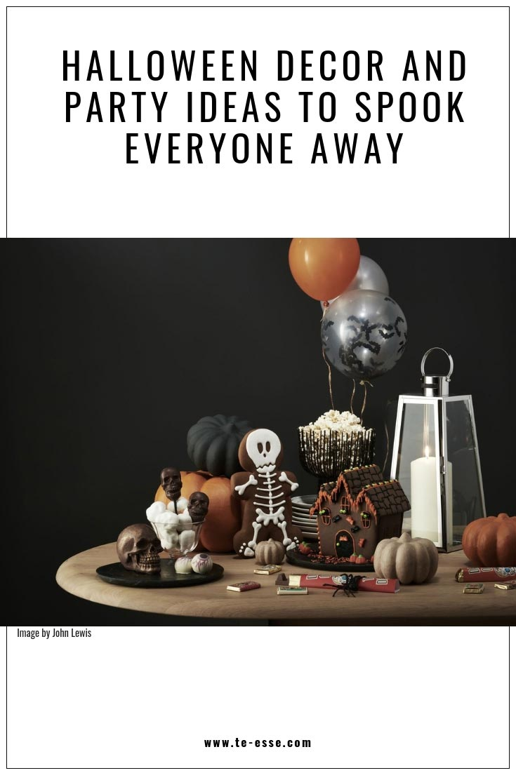 A pin graphic that reads Halloween Decor and Party Ideas to Spook Everyone Away. Image insert by John Lewis. A table with lots of Halloween candies and decor with a black background wall.