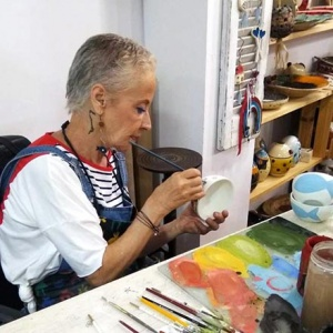 Maria Banou, a potter while painting one of her creations in her workshop. Image by Velvet.