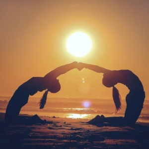two girls reaching out their hand to hold each other while arching their backs on a beach with a sun about to set.