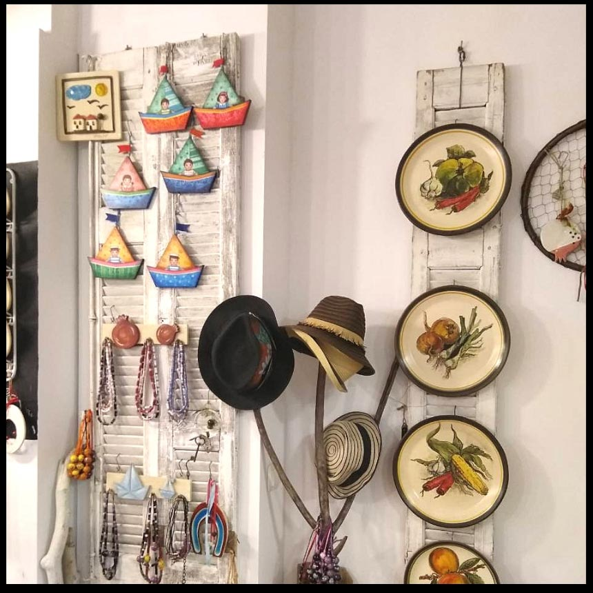 Decorative plates and boats made of clay hanging from a wall, all made by Maria Banou. Image by Velvet