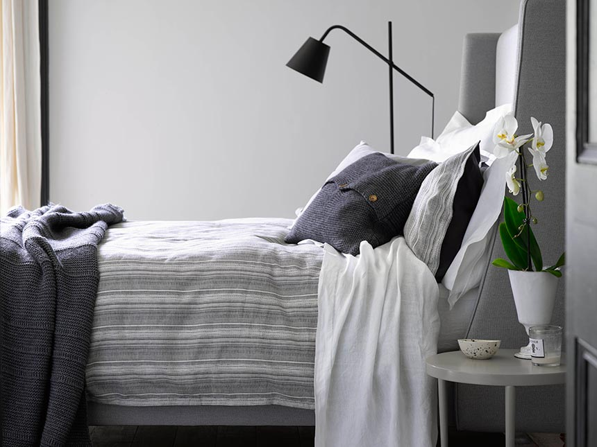 A contemporary grey bedroom that looks so calm. A few inky accents like the night lamp and throw on the bed liven it up. Image by Christy.