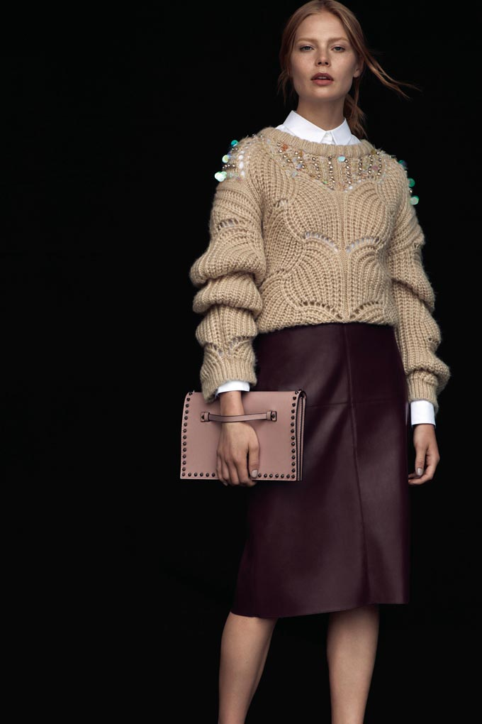 A very stylish woman wearing a white shirt with a camel sweater over a burgundy knee high skirt and a blush pink clutch. Image by Dorothy Perkins.