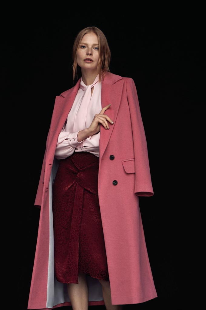 How beautiful, like an English rose. A stylish woman with a dusky rose pink overcoat, a pink silk shirt and a burgundy skirt. Image by Dorothy Perkins.