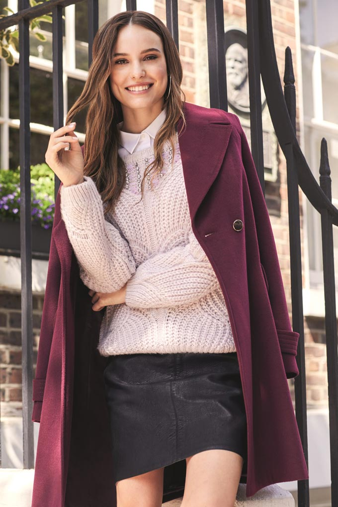 A burgundy coat looks fabulous over a pink sweater paired with a short faux leather black skirt. She looks beautiful doesn't she. Image by Dorothy Perkins.