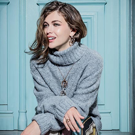 A stylish woman dressed in a grey blue sweater and a striped skirt in front of doorway. Her jewelry really update it all. Image by Folli Follie.