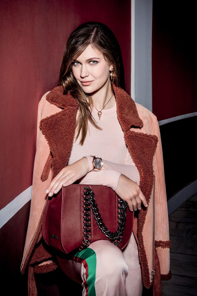 A stylish woman dressed in pink and burgundy hues. Pink sweater, pink coat with burgundy collar, pink satin track pants and a burgundy tote bag. Image by Folli Follie.