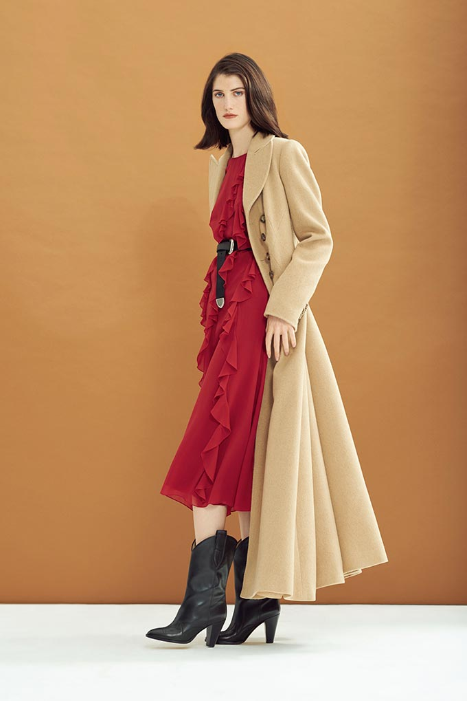 A red dress with a camel overcoat and black western boots can be a very stylish combination. Image by Hobbs.