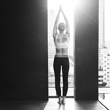 A black and white image of a woman in a sporty outfit with arms raised above her head looking out a narrow window that is from floor to ceiling and gazing at the cityscape.