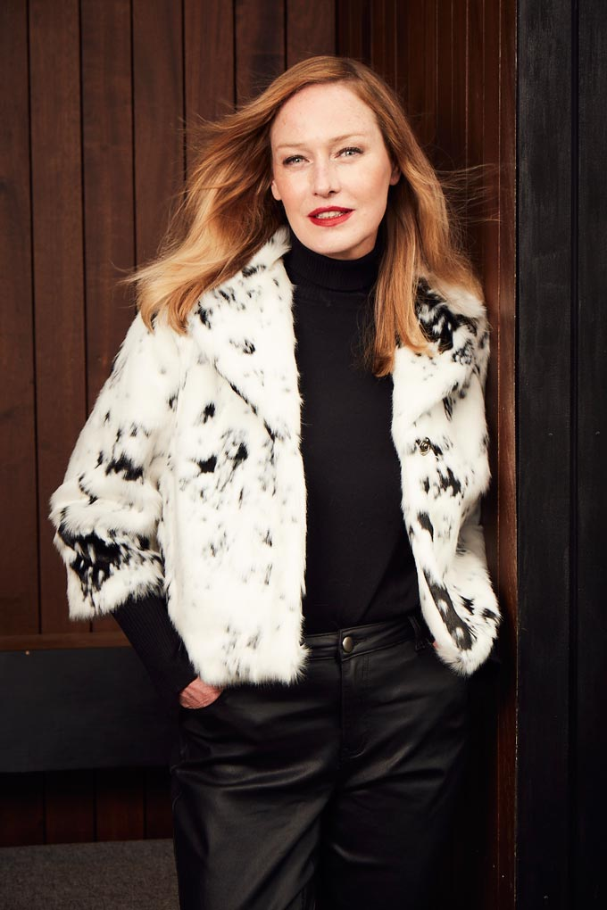 A white faux fur jacket with random black spots paired with a black outfit can look stylish and fun - just like this one. Image by JD Williams.