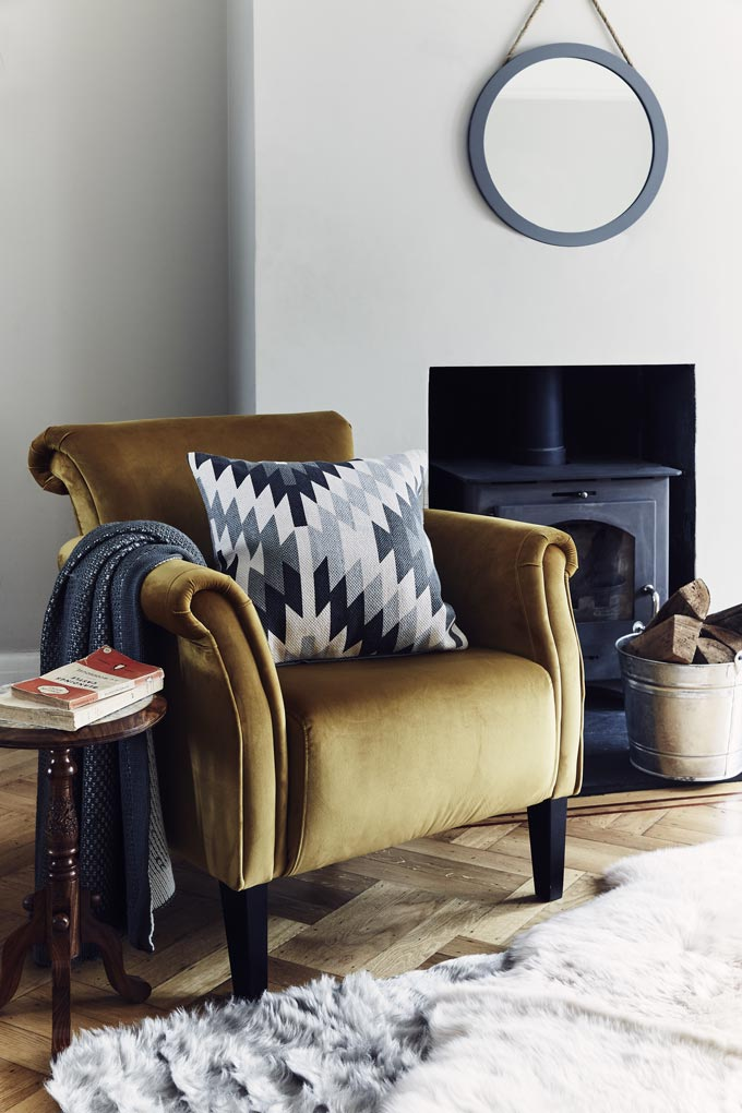 I love this velvet upholstered armchair by the fireplace. What a cozy vignette without looking rustic. Image by JD Williams Home.