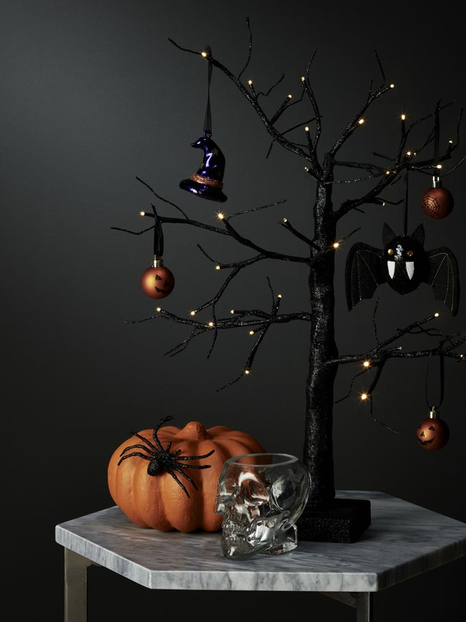 My kind of Halloween decor. Sleek and sophisticated on a marble top table. A black branch tree, a pumpkin and a silver skull. Image by John Lewis.