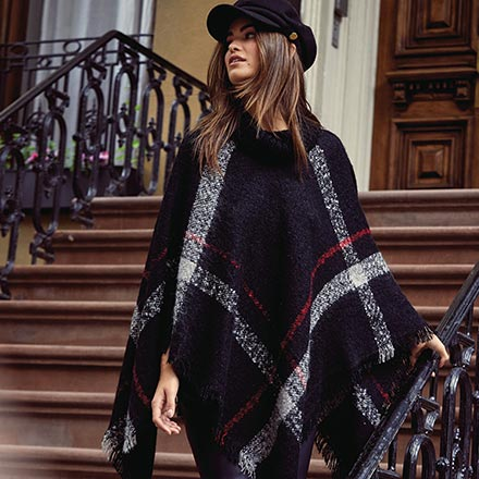 What a lovely poncho coat with a blue tartan print that looks so stylish on this woman who paired it with a black hat. Image by Lipsy.