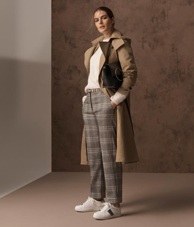 I'm not totally sure about the tartan print pants on their own, but in overall, the white sweater, the beige trench coat and the white sneakers it all looks good. Image by Marks & Spencer.