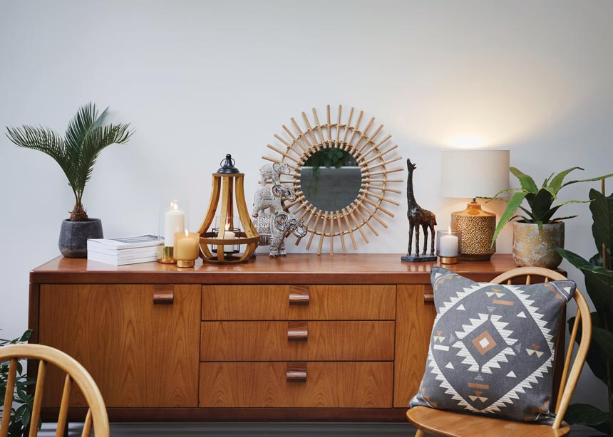 A mid century sideboard with decor against a light grey wall. Love the giraffe figurine next to the table lamp. Image by Matalan.