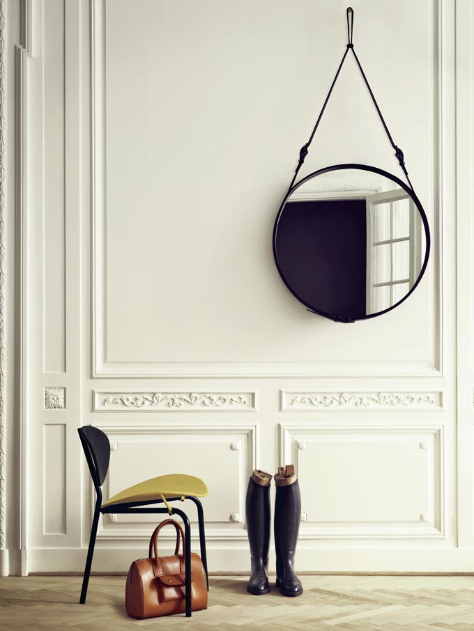 I just love the round mirror by this elegant and minimal entryway that has a chair instead of a table to anchor it and a pair of black boots. Image by Nest.