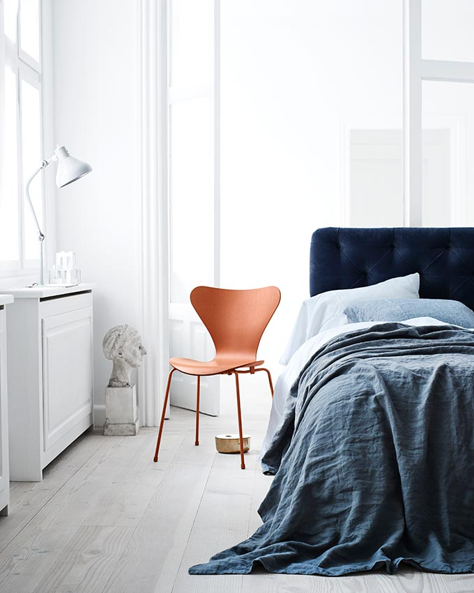 A white bedroom with a blue bed and the iconic Fritz Hansen Series 7 Chair by Arne Jacobsen looking real good. Image by Nest.