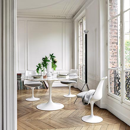 A white dining table and chairs look gorgeous in a white room with beautiful chevron parquet floor and large windows with plenty of natural light. Image by Nest.