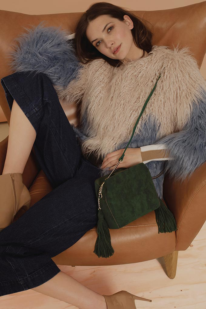 I love this color blocked shaggy faux fur jacket paired with navy blue denim pants and a green crossbody bag. Image by New Look.