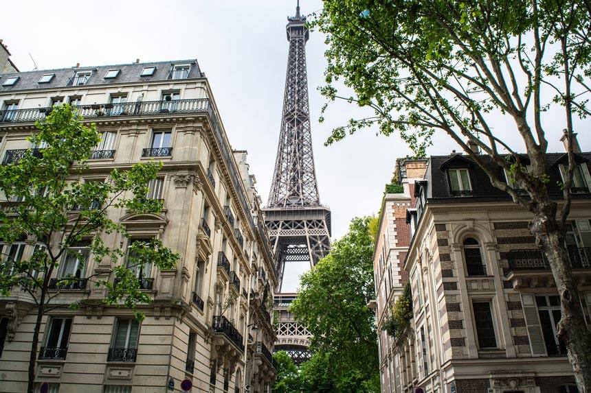 View of a street's corner buildings with the Eiffel Tower in the background.