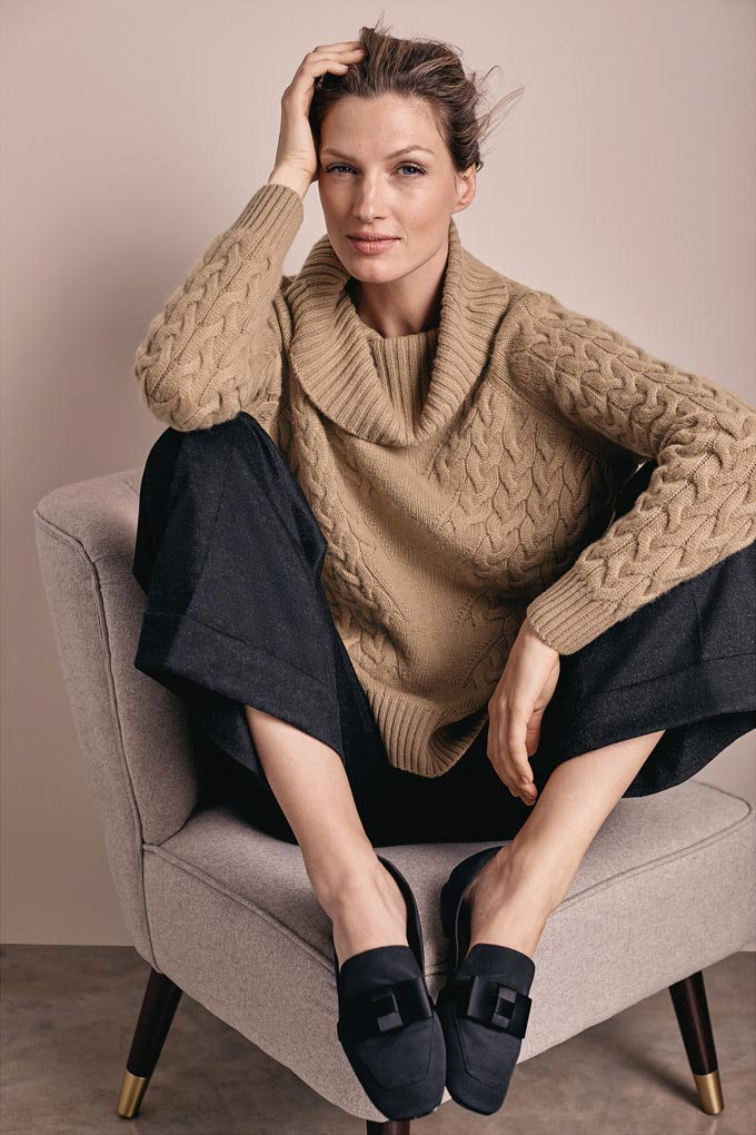 How pretty. A woman wearing a camel cord sweater paired with wide leg charcoal pants. Image by Pure Collection.