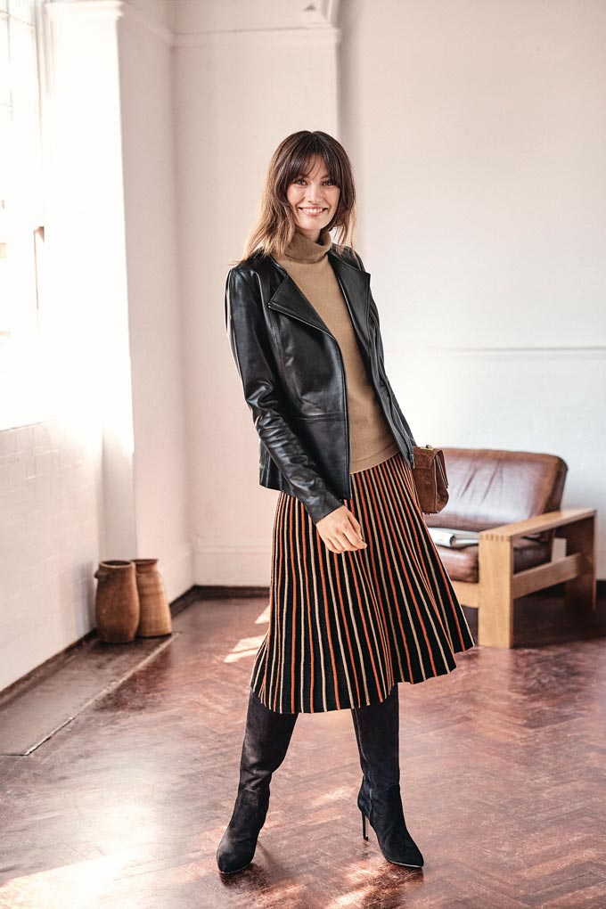 I love this outfit. A camel turtleneck sweater, a pleated knit skirt, black knee high boots and a black leather jacket. Image by Pure Collection.