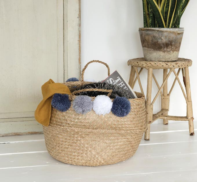 A seegrass basket with blue and white pom poms, a mustard throw and a magazine standing besides a cane stool. I love the light grey color of the hardwood flooring. Image by Rex London.