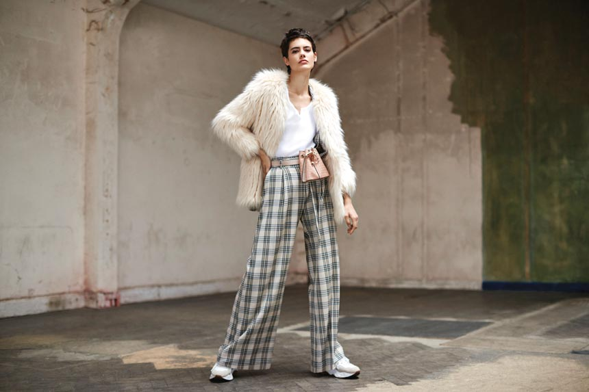 An off white faux fur jacket is always a good idea, especially when paired with check wide leg pants and sneakers. Image by River Island.