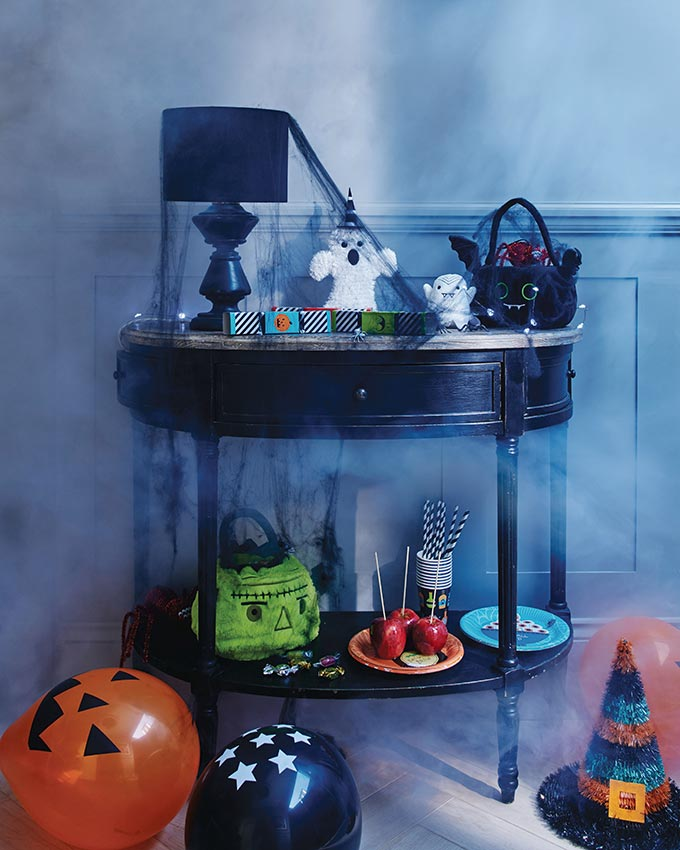 A bar cart in a vignette now looks spooky with all that Halloween decor. Image by Sainsbury's Home.