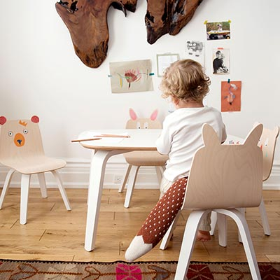 A young child appears to be busy doing something on a table in a nursery room. I love the wooden child chairs with the animals faces painted on them. How cute. Image by Cuckooland.