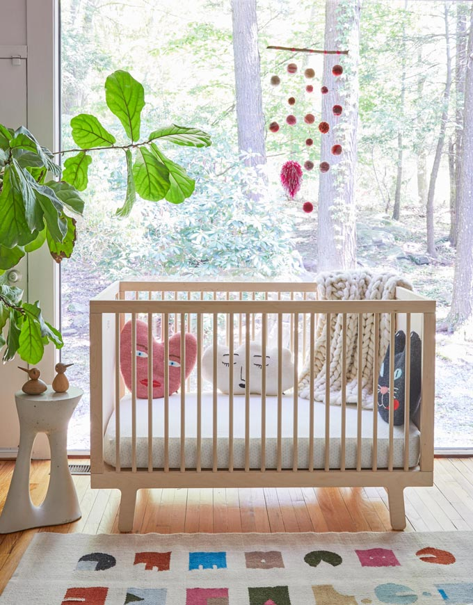 How beautiful. A crib in front of a large window with a plant besides it and heart shape pillows inside it. Image by Cuckooland.