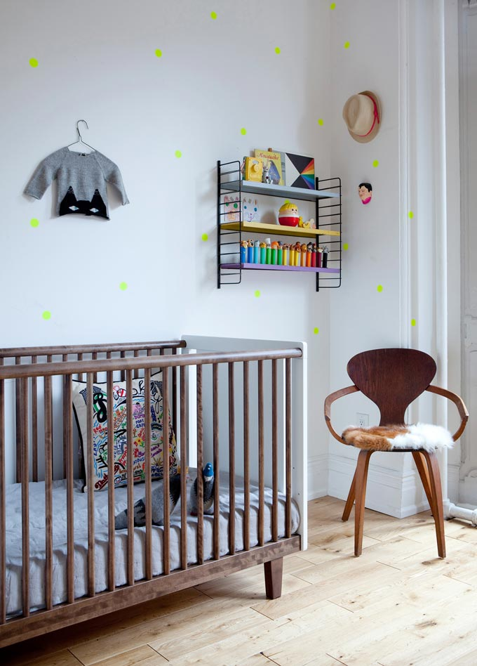 A stylish nursery room with a wooden crib and a chair besides it. Image by Cuckooland.