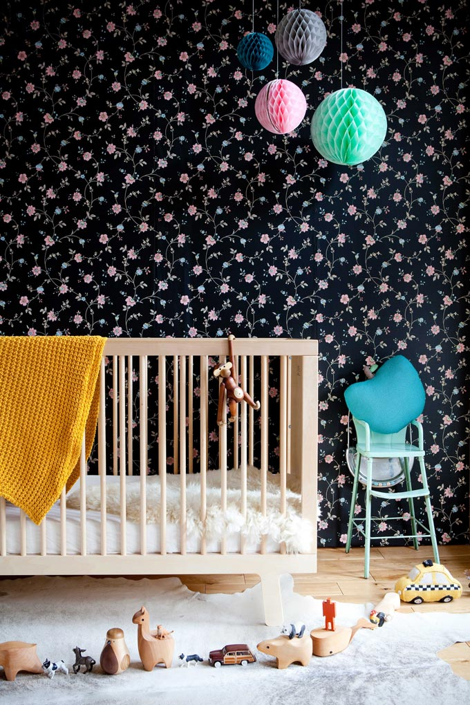 A dark blue wallpaper with a flower pattern looking amazing in a nursery room with a wooden crib and pops of color. Image by Cuckooland.