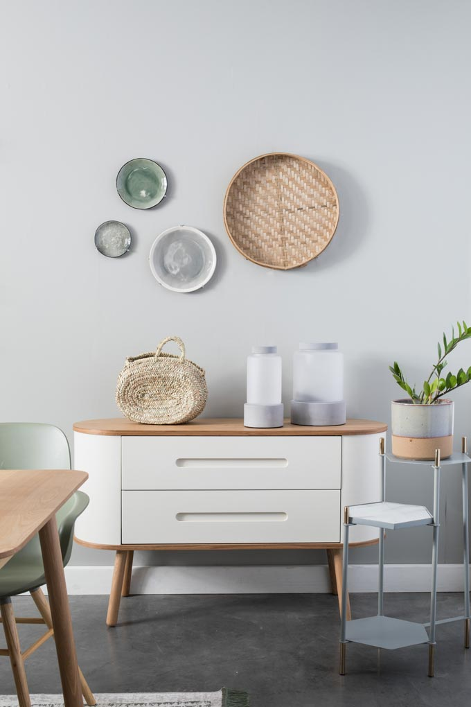 I love the organic vibe of this white sideboard with its decor and wall hangings on a light grey wall. Image by Cuckooland.