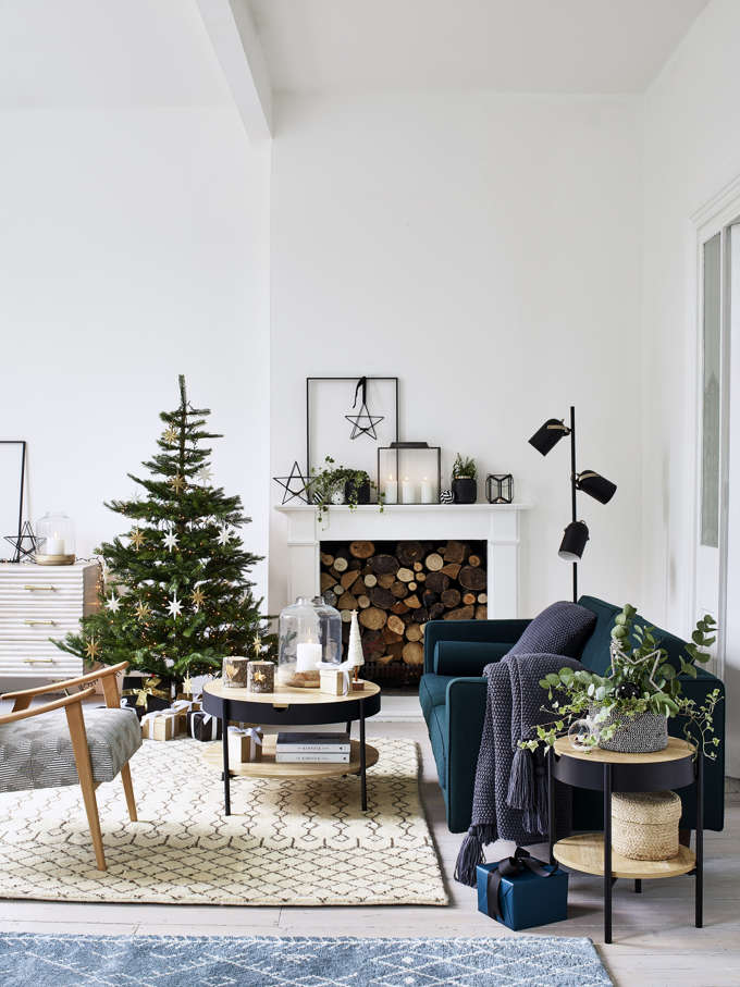 A Christmas tree by a white fireplace, styled in a minimal way, but looking good. Image by Debenhams.