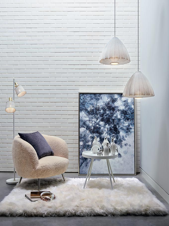 A stylish set composed of an armchair in shearling over a sheeprug, with an oversize artwork against a white brick accent wall and white pendant lights hanging over a small round side table. Image by Homesense.