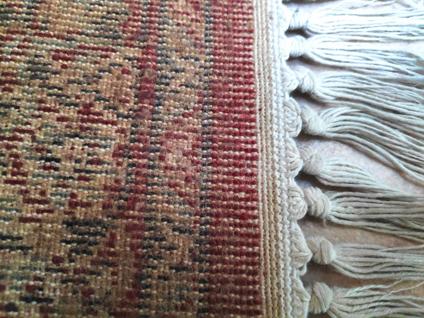 The back of a hand-knotted rug where the fringe is clearly extending out of the rug's foundation. Image by Velvet.